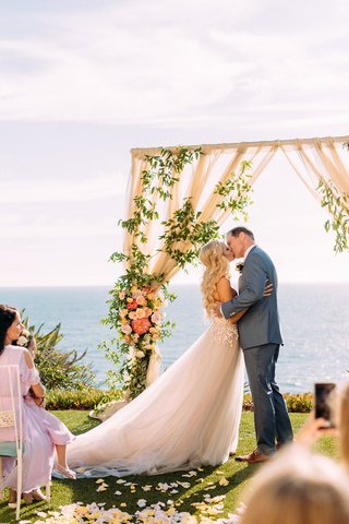 bride-in-custom-trish-peng-wedding-dress-groom-grey-suit-kiss-ocean-view-ceremony-pastel-decor