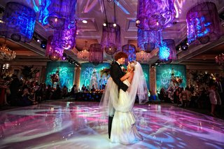 bride-in-anne-barge-holds-veil-during-first-dance-on-vibrant-dance-floor