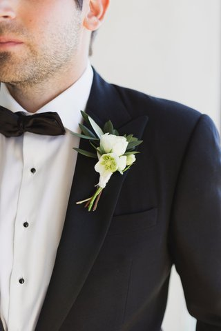 groom-boutonniere-with-white-flowers-with-dark-green-leaves