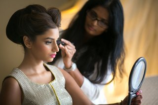 indian-american-bride-looks-in-mirror-as-makeup-artist-applies-mascara