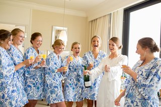bride-in-white-robe-bridesmaids-in-blue-and-white-floral-robes-mimosas-while-getting-ready