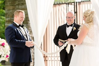 bride-and-groom-holding-strong-cord-unity-braid-uncle-performing-ceremony-officiant-custom-tradition