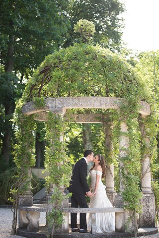 bride-in-off-shoulder-pnina-tornai-wedding-dress-kissing-groom-in-tuxedo-at-oheka-castle-under-dome