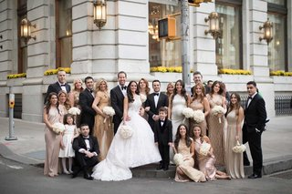 bride-and-groom-with-wedding-party-gold-dresses-tuxedos-bow-ties-white-flowers-ring-bearers-flower