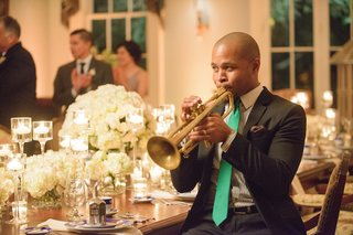 man-playing-gold-trumpet-at-dining-room-table