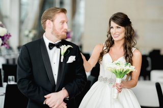 bride-walking-up-to-groom-and-tapping-him-on-shoulder-during-first-look-in-reception-space