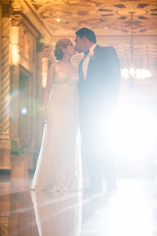 bride-in-a-beaded-high-waisted-jenny-packham-dress-and-updo-kisses-groom-in-black-tuxedo