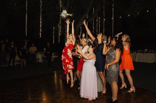 group-of-women-at-wedding-reception-leaping-for-the-bridal-bouquet