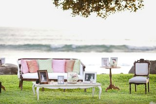 coffee-table-chair-sofa-with-pink-green-pillows-and-family-photos-on-grass-lawn