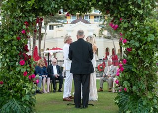 bride-and-groom-with-officiant-at-small-ceremony-acqualina-resort-and-spa-greenery-arch-pink-roses