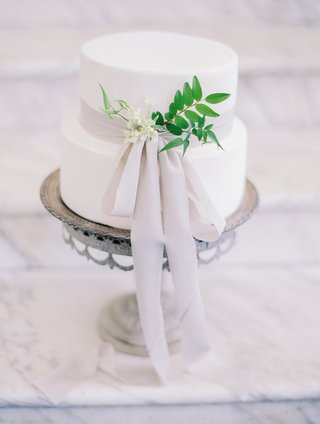 small-white-wedding-cake-with-light-grey-ribbon-small-white-flowers-greenery-on-silver-cake-stand