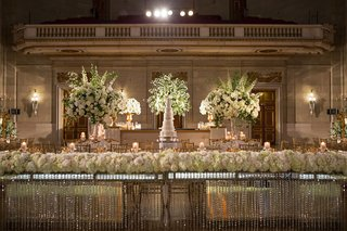 head-table-with-crystals-dangling-white-flower-runner-seven-layer-white-cake-and-flowers
