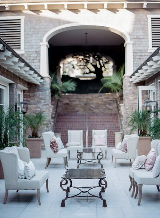 outdoor-wedding-lounge-area-with-white-chairs-ruffled-pillows-in-pink-and-ivory