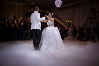 bride-and-groom-first-dance-with-fog-machine-ball-gown-headpiece-white-groom-jacket-chandelier