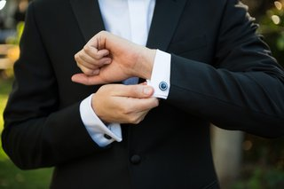 groom-in-classic-black-tuxedo-shows-round-cuff-links