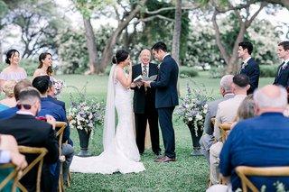 bride-and-groom-wedding-ceremony-vow-exchange-happy-officiant-bridesmaids-groomsmen-guests-sunglasse