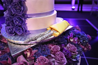white-wedding-cake-with-purple-sugar-roses-crystals-silver-handled-cake-server-set-in-gold-napkin