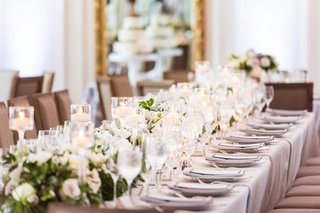 wedding-reception-table-light-grey-linens-flower-runner-candles-in-glass-votives