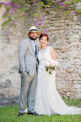 bride-in-high-neck-beaded-wedding-dress-white-pink-bouquet-groom-in-light-grey-suit-fedora
