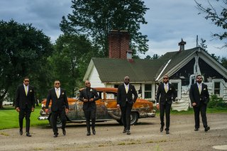 groom-and-groomsmen-in-black-suits-in-front-of-rusted-vintage-car