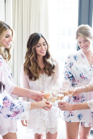 getting-ready-photo-of-bride-and-bridesmaids-in-robes-toasting-cheers-champagne-bridal-suite