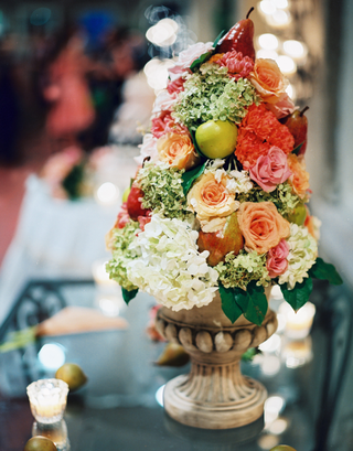 stone-urn-filled-with-rose-and-hydrangea-flowers-and-apple-and-pear-fruits