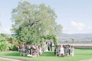 wedding-ceremony-tuscany-florence-italy-intimate-outdoor-ceremony-greenery-arbor-white-chairs-guests