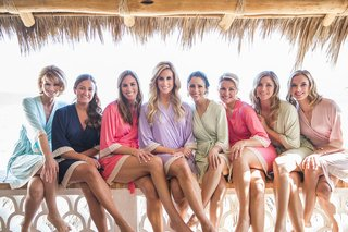 a-bride-and-her-bridesmaids-sitting-on-railing-of-hotel-in-mexico-in-blue-pink-purple-green-robes