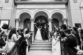 black-and-white-photo-of-bride-and-groom-leaving-greek-orthodox-church-wedding-ceremony-guests