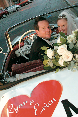 newlyweds-in-decorated-vintage-automobile