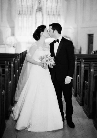black-and-white-photo-of-couple-kissing-in-church-aisle-empty-pews-saint-james-chapel-wedding