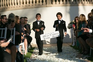 young-boys-in-tuxedos-walking-down-the-aisle-with-poster