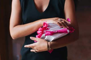 wedding-guest-holding-pile-of-wedding-ceremony-programs-tied-with-bright-pink-ribbon-bows
