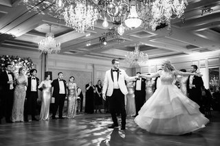 black-and-white-photo-of-bride-and-groom-on-dance-floor-first-dance-ball-gown-chandelier