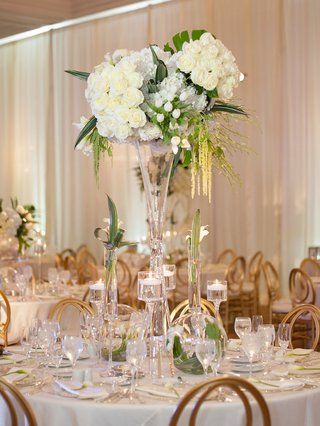 round-table-with-tall-white-centerpiece-green-leaves-tropical-amaranthus-gold-chairs-floating-candle