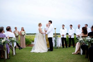 couple-marries-coastal-wedding-guests-family-bridesmaids-groomsmen-champagne-dress-white-suit-jacket