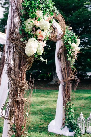 arbor-made-up-of-winding-branches-greenery-and-white-and-pink-flowers-with-sheer-white-fabric
