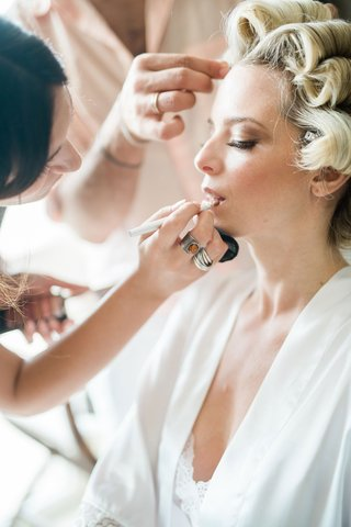 blonde-bride-with-hair-in-curlers-while-getting-her-makeup-done