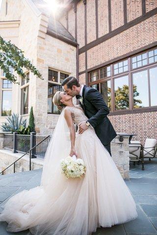 couple-kisses-after-ceremony-monique-lhuillier-dress
