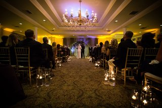 indoor-wedding-with-warm-lining-aisle-lined-by-floating-candles