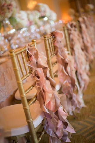 pink-ruffle-ribbon-fabric-on-back-of-gold-reception-chairs