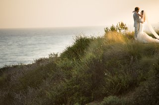 bride-and-groom-hug-on-california-coast-cliff