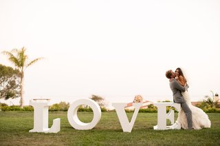 southern-california-bride-and-groom-next-to-love-letters
