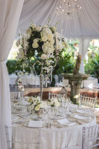 tall-silver-candelabra-centerpiece-with-greenery-white-flowers-chandelier-crystals-and-clear-chairs