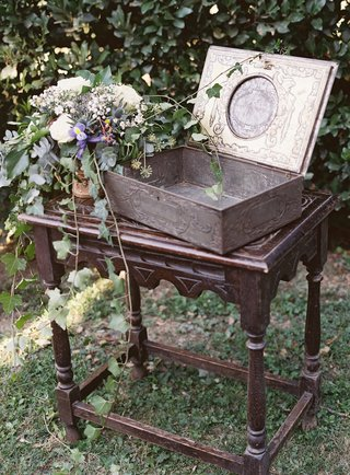 wedding-card-and-gift-display-at-outdoor-reception-greenery-purple-white-flowers-antique-dark-wood