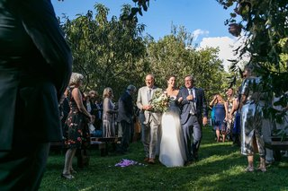bride-walking-down-grass-aisle-with-dad-and-stepdad-in-grey-suits-guests-standing