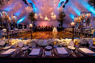tented-reception-with-crystal-chandeliers-over-dance-floor-blue-lighting-tan-damask-projections