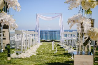 white-florals-seating-and-archway-for-a-seaside-ceremony