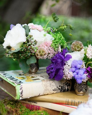 outdoor-wedding-reception-table-with-white-and-purple-flowers-in-small-vases-on-books