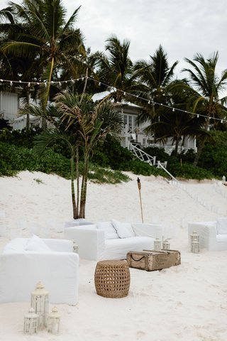 wedding-reception-lounge-area-white-sofa-cover-wood-table-lanterns-bistro-lights-green-palms
